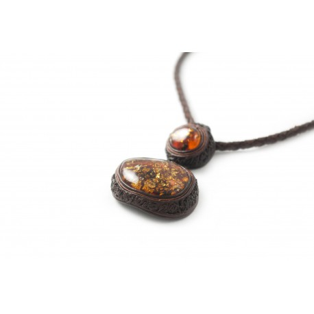 Hand-made piece of leather jewelry decorated with amber